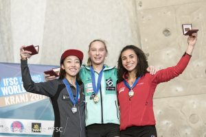 Janja Garnbret standing center podium after placing first in the women's lead finals ahead of Jain Kim (left), second place, and Molly Thompson-Smith (right), third place. Photo: Eddie Fowke/IFSC.