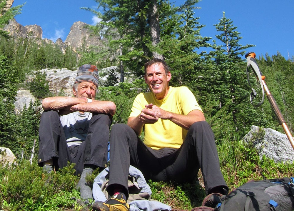 Beckey and the author chat with the West Face of North Early Winter Spire in the background. Photo courtesy of Mark Kroese.